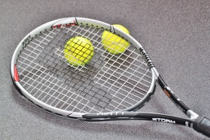 TENNIS RACKET WITH TWO BALLS SPEWED FROM BLACK HOLE